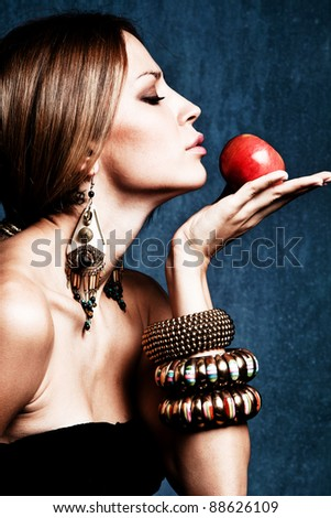 woman with oriental jewelry hold an apple, profile, studio shot - stock photo
