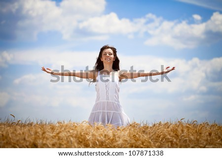woman with outstretched arms enjoying in summer field