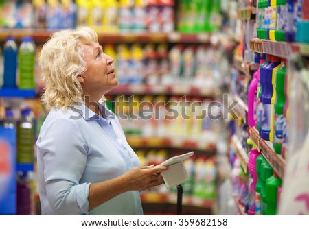 Woman with pad shopping for household detergents - stock photo