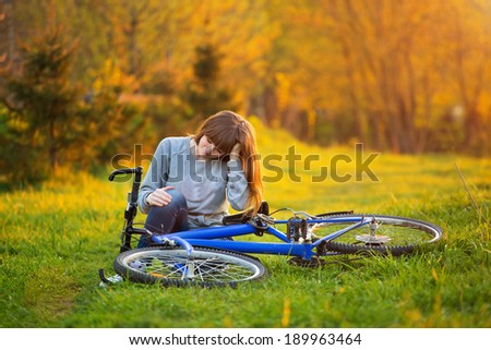 Woman with pain in knee joints after biking on bicycle in park at sunset. Girl sitting down with painful face expression. Knee pain bike injury. - stock photo