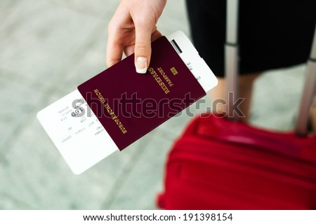 woman with passport and airline tickets at an airport waiting for her departure on holiday. - stock photo