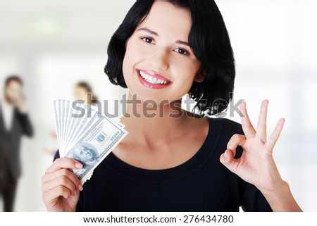 Woman with perfect gesture holding dollar banknotes.