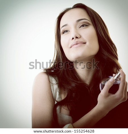 Woman with perfume, young beautiful girl holding bottle of perfume and smelling aroma, toned - stock photo