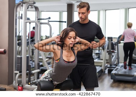 woman with personal trainer flexing muscles in gym