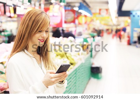 Woman with phone in grocery aisle. Hipster girl using mobile in store aisle. Shopping app concept.