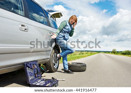 Woman with phone is calling in service of spare tire his car
