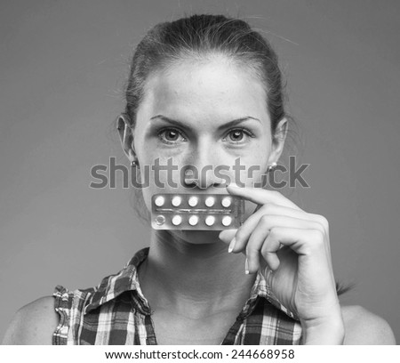 woman with pills in hand studio black and white - stock photo