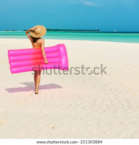 Woman with pink inflatable raft walking at the beach - stock photo