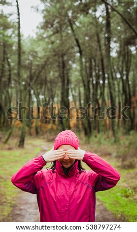 Woman with pink wool hat in the forest covering her eyes