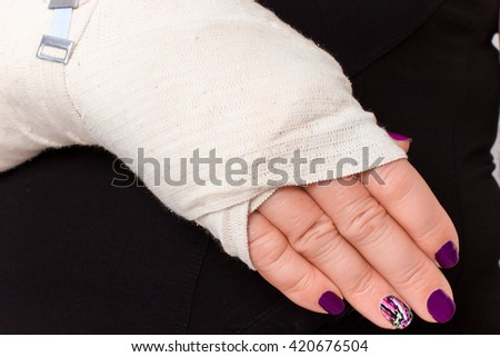 Woman with plastered hand on a white background