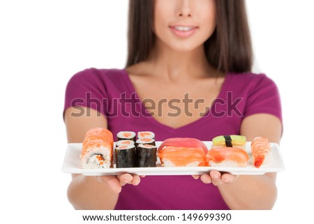 Woman with plate of sushi. Beautiful mixed race woman holding a plate of sushi while standing isolated on white - stock photo