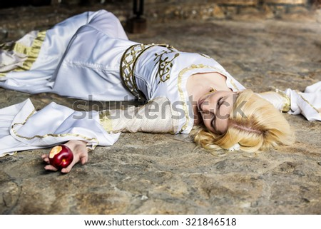 Woman with poisoned apple lies on sand - stock photo