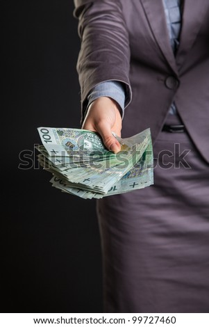 Woman with polish zloty money on dark gray background - stock photo