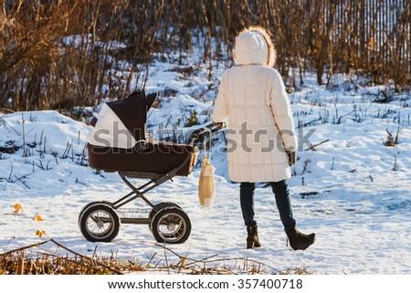 Woman with pram winter outdoors. - stock photo