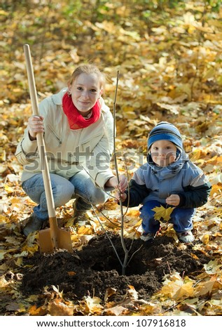 woman with  preschooler son setting tree in autumn garden