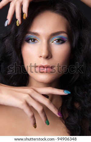 Woman with professional colourful make-up and sparkling manicure - stock photo