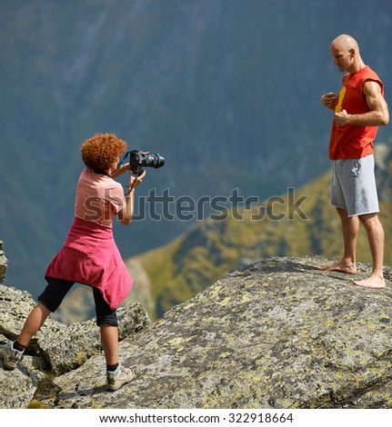 Woman with professional photo camera taking picture of a sporty man on the mountains - stock photo