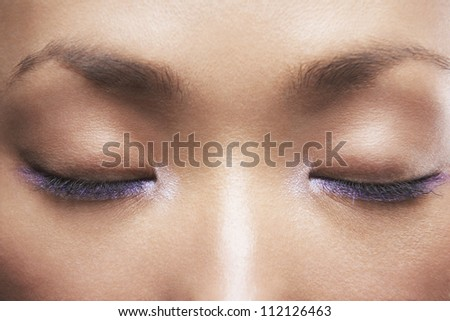 Woman with purple eyeliner, eyes closed