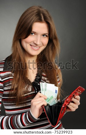 woman with purse and paper money on a grey background - stock photo