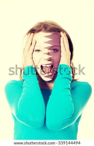 Woman with Qatar flag painted on face. - stock photo