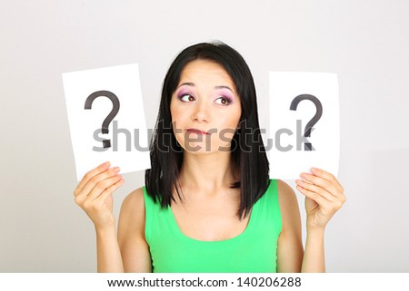 Woman with question marks on grey background