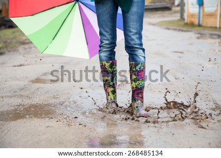 Woman with rain boots jumps into a puddle - stock photo
