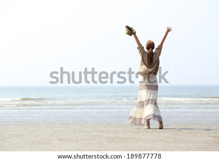 Woman with raised arms at the beach celebration from behind - stock photo