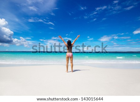 woman with raised hands on the beach - stock photo