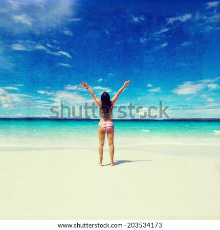woman with raised hands on the beach. vintage effect