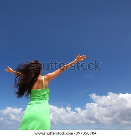 Woman with raised hands over blue sky background - stock photo