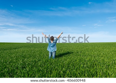 Woman with raised hands  standing back in green field against blue sky