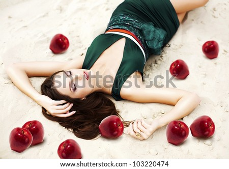 woman with red apples on the sand in green dress - stock photo