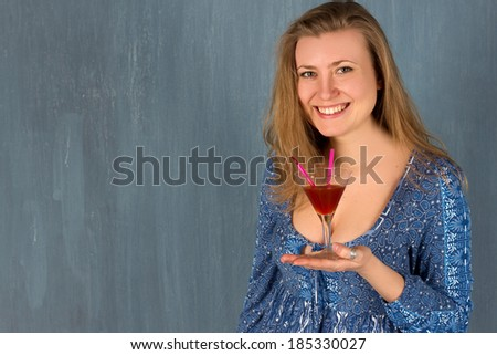 woman with red cocktail glass. Blue wall.
