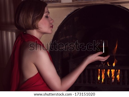 woman with red dress sitting near fireplace with wine - stock photo