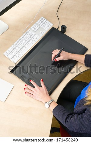 Woman with red finger nails working behind a grapic tablet, busy with computer aided design - stock photo