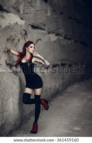 woman with red hair, huge devil horns decorates her head. Portrait of the beautiful young woman in devil carnival shape - stock photo