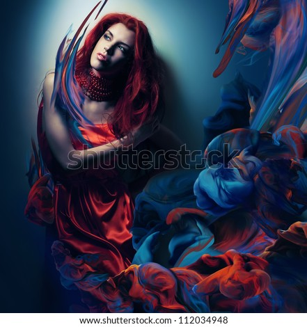 woman with red hair in paint waves - stock photo