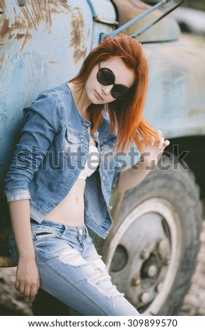 woman with red hair near grunge old truck, selective focus  - stock photo