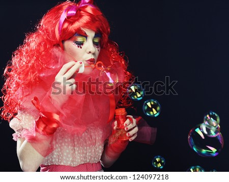 woman with red hair with creative make-up blowing soap bubbles. - stock photo