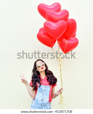 Woman with red heart balloon. Beautiful girl with bunch of hearts outdoors.
