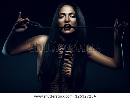 woman with red lips biting whip - stock photo