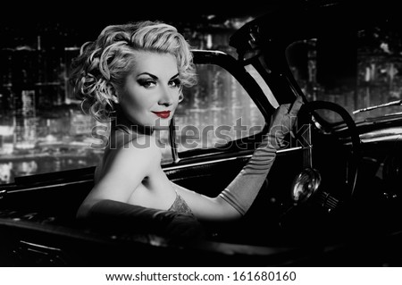 Woman with red lips in retro car against night city - stock photo
