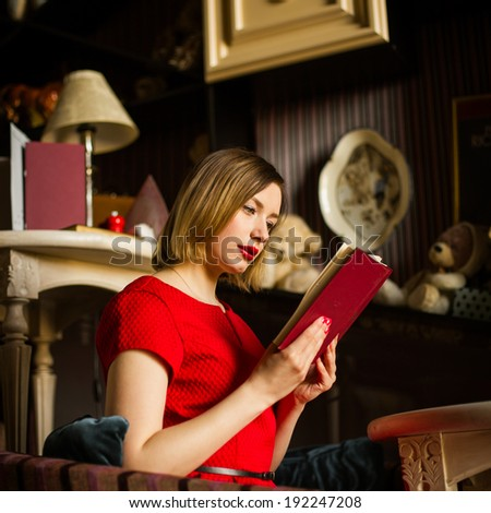 woman with red lipstick sitting in a restaurant and reading a novel - stock photo