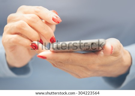 Woman with red manicure using smartphone. Horizontal photo
