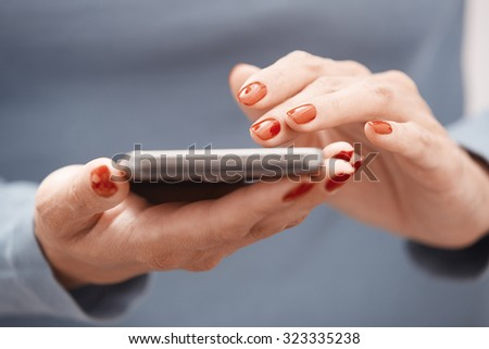 Woman with red manicure using smartphone. Horizontal photo - stock photo