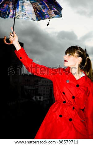 woman with red raincoat and umbrella in city