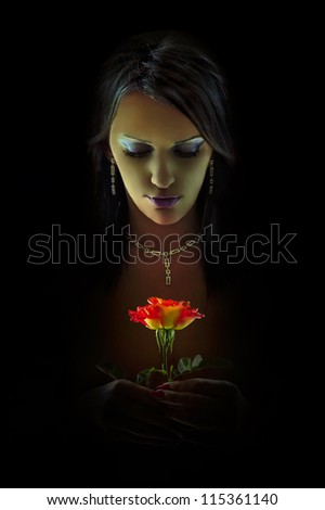 Woman with red rose in the shadows - stock photo
