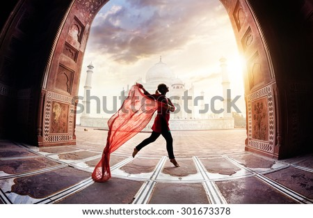 Woman with red scarf dancing near Taj Mahal in Agra, Uttar Pradesh, India - stock photo