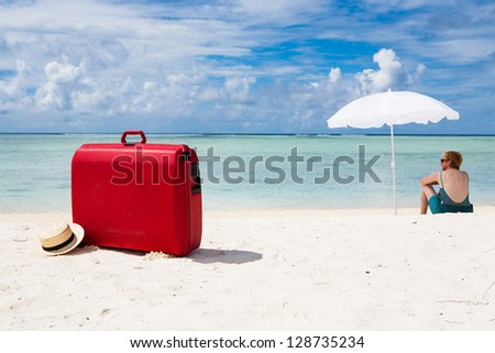 woman with red suitcase sitting under a white sunshade at the beach - stock photo