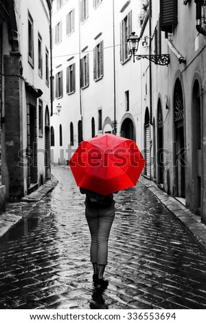 Woman with red umbrella on cobblestone street in the old town. Wind, rain, stormy weather. Color in black and white conceptual, idea. Vintage, retro style. - stock photo